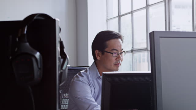 MS businessman sitting at desk in office of high tech startup looking at computer monitor
