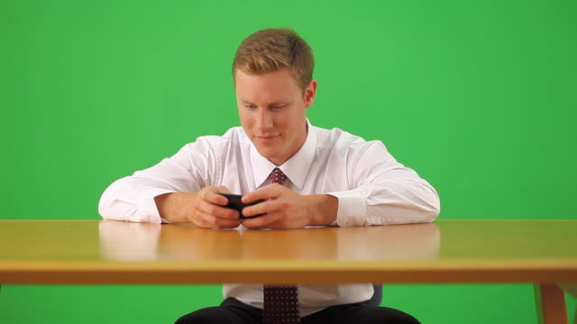 businessman sitting at desk text messaging on cell phone - text messaging video stock e b–roll