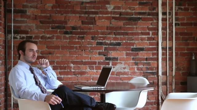 vídeos y material grabado en eventos de stock de ms businessman sitting at table in office with laptop looking out window/seattle, washington, usa - duda