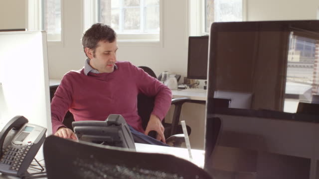ms businessman sitting at workstation in office answering text message on smart phone - maroon stock videos and b-roll footage