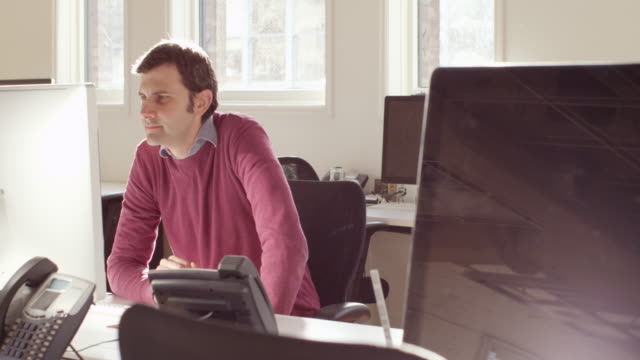MS TD Businessman sitting down at workstation in office to start working on computer