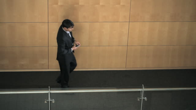 Businessman sitting down in corridor and making call on cellphone