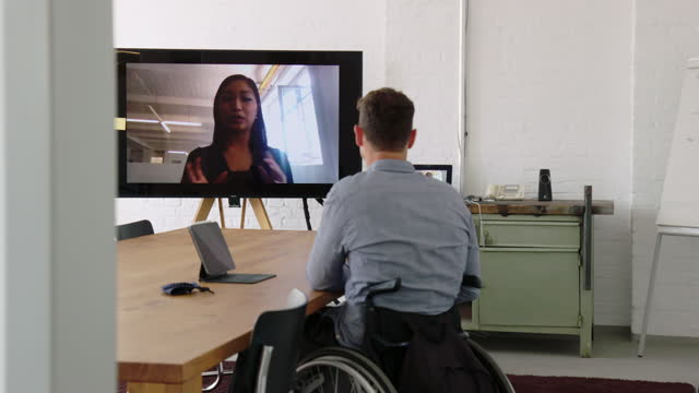 businessman sitting in a wheelchair having a online meeting with a colleague - white collar worker stock videos & royalty-free footage