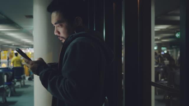 空港に座り、夜に携帯電話を使って仕事をするビジネスマン。 - 寄りかかる点の映像素材/bロール