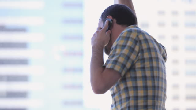 vídeos de stock, filmes e b-roll de ms tu pan businessman sitting in chair at office workstation talking on smart phone walking to windows to look out - desaparecer gradualmente