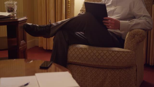 MS TU Businessman sitting in chair in hotel room working on digital tablet