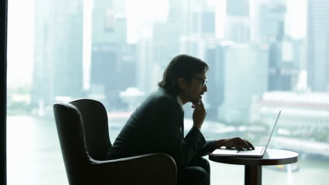 WS Businessman sitting in front of cityscape working on laptop computer