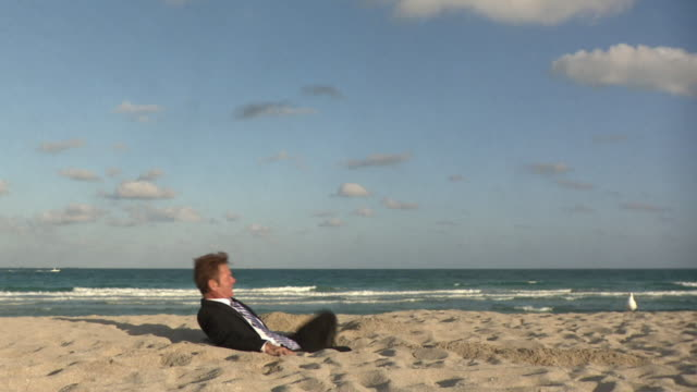 ws businessman sitting in hole at beach / south beach, florida, usa - legs crossed at ankle stock videos and b-roll footage