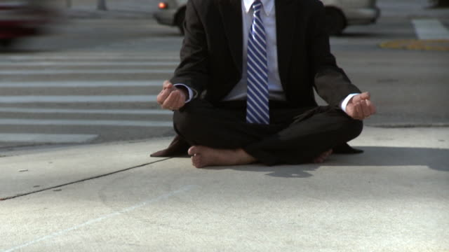MS PAN Businessman sitting in lotus position on pavement / South Beach, Florida, USA