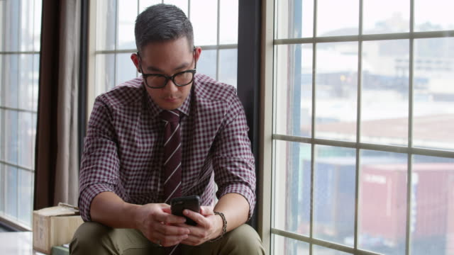MS Businessman sitting near windows in office looking at smartphone
