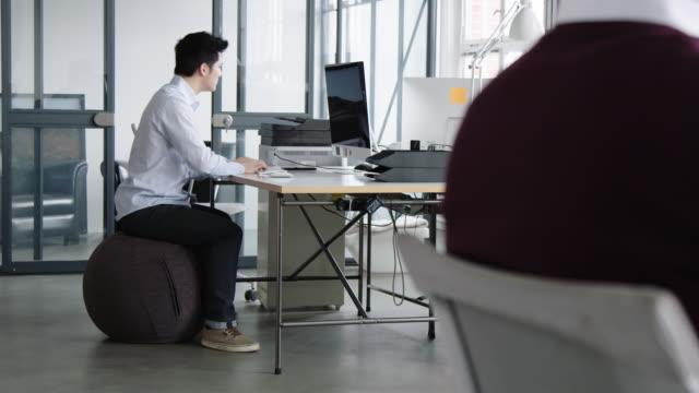 vidéos et rushes de homme d'affaires s'asseyant sur une chaise de boule et travaillant sur l'ordinateur - sitting