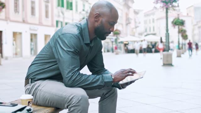Hombre de negocios sentado en un banco y usando tableta digital en la ciudad