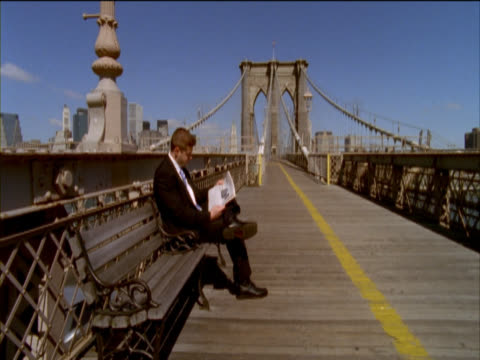 Businessman Sitting on a Bench Reading a Newspaper, Rising and Walking Away and a Cyclist on Brooklyn Bridge, New York, USA