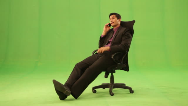 vidéos et rushes de businessman sitting on a chair and talking on a mobile phone  - costume