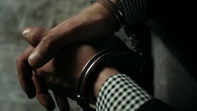 Zakenman zittend op bed in de gevangeniscel
