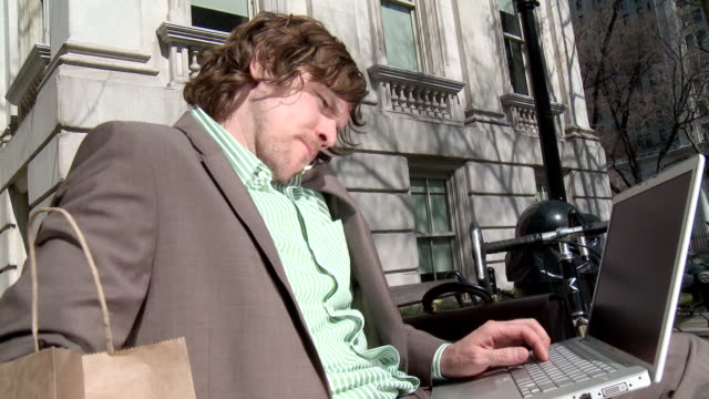 ms businessman sitting on bench, using laptop and talking on phone, new york city, new york, usa - multi tasking stock videos & royalty-free footage