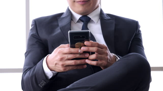 businessman sitting on chairs in modern office lobby, waiting too long for job interview, using technology devices. - job search stock videos and b-roll footage