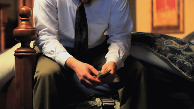 ms businessman sitting on edge of bed and counting money, appleton, wisconsin, usa - ウィスコンシン州アップルトン点の映像素材/bロール