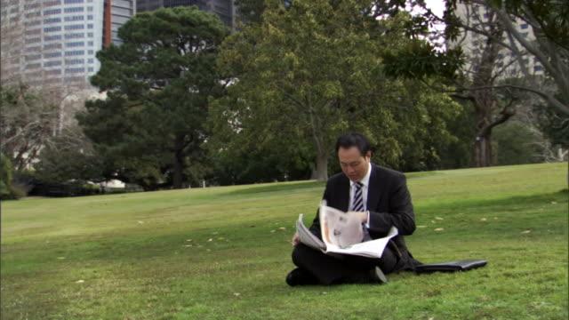 ms, businessman sitting on lawn in park, reading newspaper, sydney, australia - 座る点の映像素材/bロール