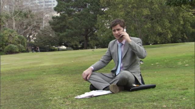 ms, businessman sitting on lawn in park, talking on mobile phone, sydney, australia - 座る点の映像素材/bロール