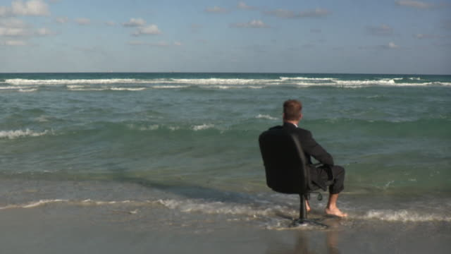 WS Businessman sitting on office chair at beach and turning / South Beach, Florida, USA