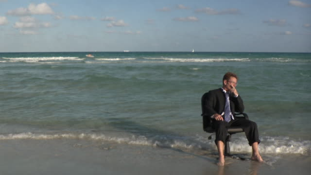 WS Businessman sitting on office chair at beach / South Beach, Florida, USA