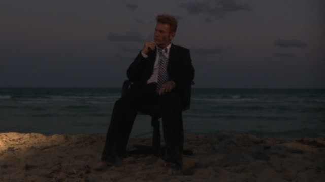 WS SLO MO Businessman sitting on office chair at beach / South Beach, Florida, USA
