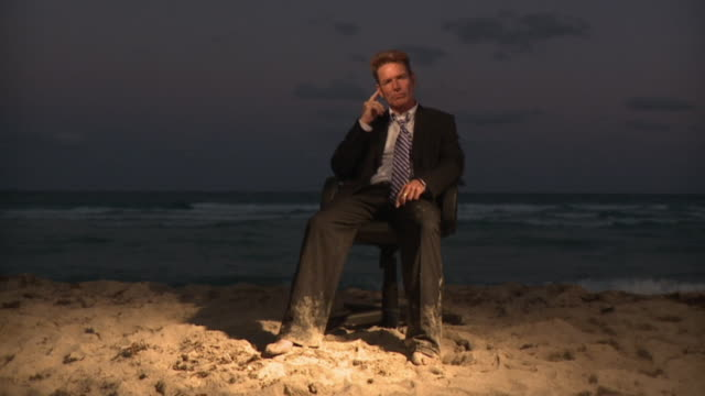 ws slo mo businessman sitting on office chair at beach / south beach, florida, usa - disappointment stock videos & royalty-free footage