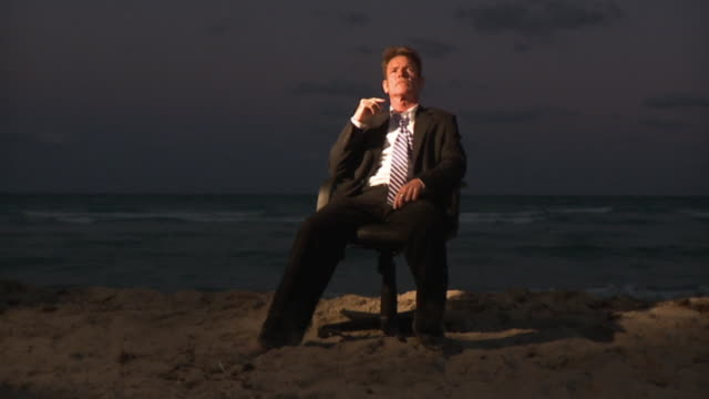 vídeos de stock, filmes e b-roll de ws slo mo businessman sitting on office chair at beach / south beach, florida, usa - cabeça para trás