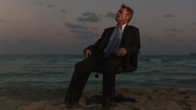 ms slo mo businessman sitting on office chair at beach / south beach, florida, usa - disappointment stock videos & royalty-free footage