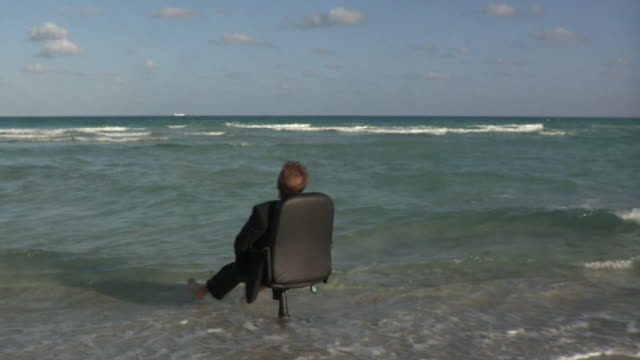 ws businessman sitting on office chair in sea, turning around / south beach, florida, usa - out of context stock videos & royalty-free footage