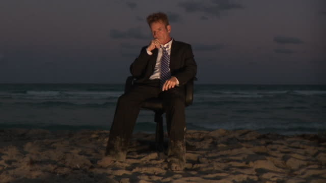 WS SLO MO Businessman sitting on office chair on beach and thinking hard / South Beach, Florida, USA