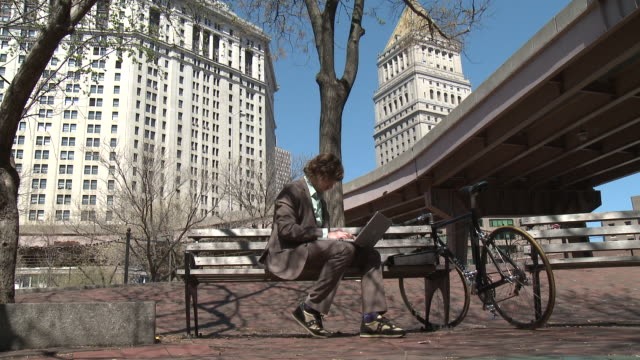 ws businessman sitting on park bench using laptop, new york city, new york, usa - wide shot stock videos & royalty-free footage
