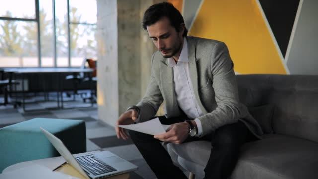 geschäftsmann sitzt auf sofa im büro und mit laptop - akte stock-videos und b-roll-filmmaterial
