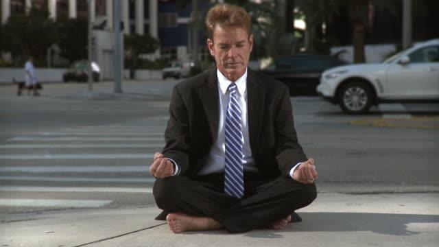 MS Businessman sitting on street corner in lotus position / South Beach, Florida, USA