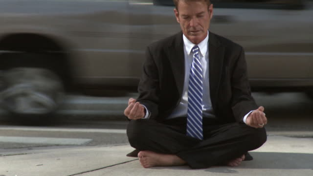 ms pan businessman sitting on street corner in lotus position / south beach, florida, usa - only mature men stock videos & royalty-free footage