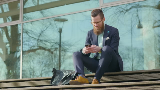 businessman sitting outdoors using his smart phone - positive emotion stock videos & royalty-free footage