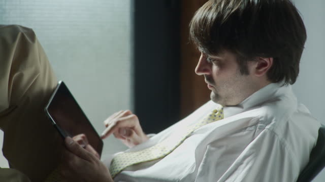 MS TD Businessman sitting writing email on digital tablet / Brooklyn, New York, USA