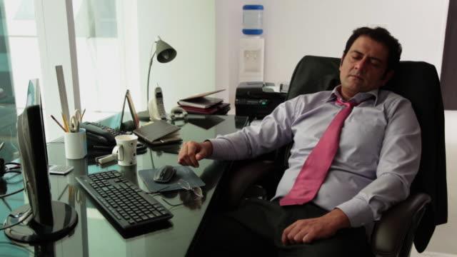 businessman sleeping in an office  - コードレスフォン点の映像素材/bロール