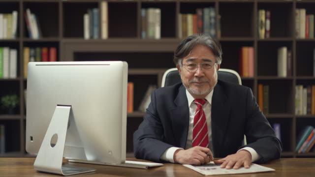 A businessman smiling and writing his signature in the office