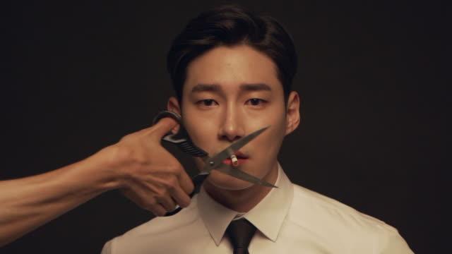 vidéos et rushes de a businessman smoking and the cigarette is cut down by scissors - manque