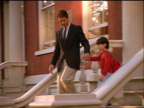 vídeos de stock, filmes e b-roll de businessman + son holding hands walking down front steps of building - 1990 1999