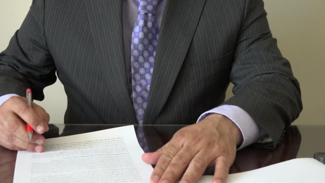 businessman spell checking or proofreading a document over his desk - pen and ink stock videos & royalty-free footage