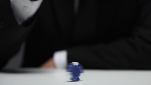 vídeos y material grabado en eventos de stock de businessman spinning a poker chip in the game - casino