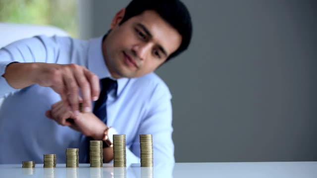 businessman stacking coins on table, delhi, india - positioning stock videos & royalty-free footage