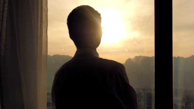 Geschäftsmann steht und schaut auf Sonnenuntergang