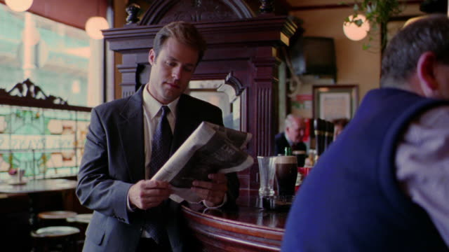 businessman standing at bar reading newspaper / dublin, ireland - giornale video stock e b–roll