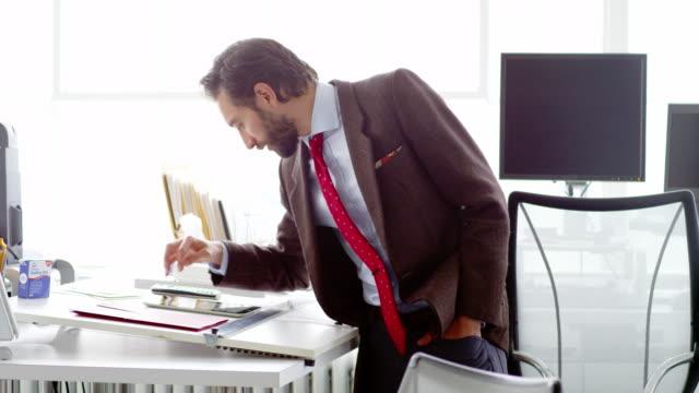 vídeos de stock e filmes b-roll de ms businessman standing at table in office working on digital tablet - vestuário de trabalho formal