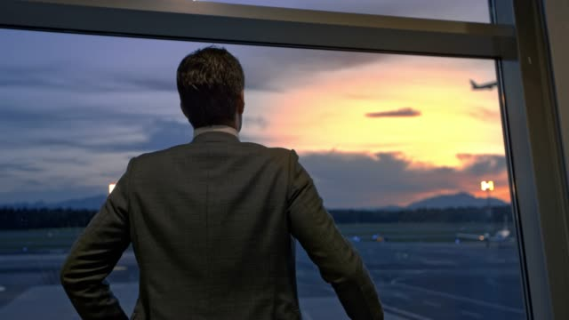 businessman standing at the window at the airport and observing the planes at sunset - part of a series stock videos & royalty-free footage