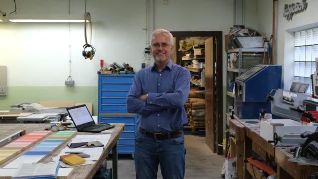 vídeos de stock e filmes b-roll de businessman standing by a workbench in workshop - retrato formal
